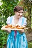 拿着椒盐脆饼的少女装礼服的愉快的美丽的妇女 免版税库存照片