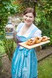 拿着椒盐脆饼的少女装礼服的愉快的美丽的妇女 库存图片