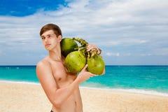 拿着椰子的愉快的英俊的年轻男性海滩在太阳o下 免版税库存图片