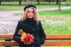 拿着槭树叶子和一本书的外套的女孩在澳大利亚的公园 图库摄影