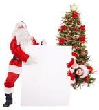 拿着横幅的圣诞老人和女孩由圣诞树。 免版税图库摄影