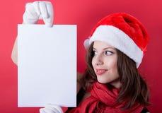 拿着横幅的圣诞老人帽子的圣诞节女孩。 库存照片