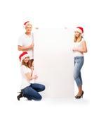 拿着横幅的圣诞节帽子的三个愉快的少年 库存照片
