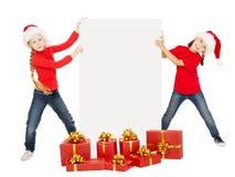 拿着横幅的愉快的圣诞节孩子 与海报的圣诞老人帮手 库存照片