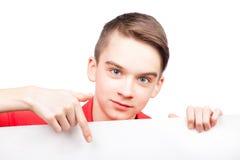拿着横幅的青少年的男孩指向在白色隔绝的手指 免版税库存图片