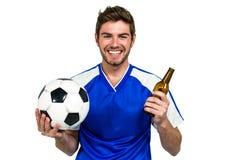 拿着橄榄球和啤酒瓶的微笑的人 免版税图库摄影