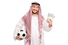 拿着橄榄球和金钱的年轻阿拉伯人 免版税库存图片