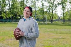 拿着橄榄球球的年轻微笑的运动员 免版税库存照片