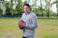 拿着橄榄球球的年轻运动员 图库摄影