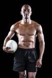 拿着橄榄球球的赤裸上身的运动员画象 库存图片