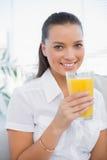拿着橙汁的快乐的俏丽的妇女坐舒适长沙发 免版税库存图片