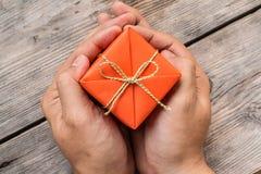 拿着橙色礼物盒和黄色丝带的手 免版税库存照片
