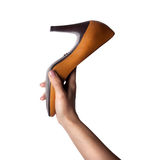 拿着橙色鞋子的女性手 图库摄影