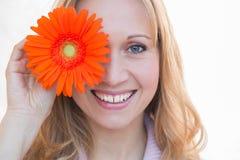 拿着橙色延命菊的美丽的妇女 库存图片