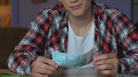 拿着欧元钞票,坐的家庭桌,财政责任的男生 影视素材