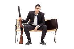 拿着步枪的生气商人供以座位在长凳 库存照片