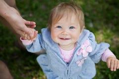 拿着母亲的小逗人喜爱的女孩由手 图库摄影