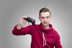 拿着比赛控制器的年轻人 免版税库存照片