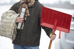 拿着毯子和热水瓶的驾驶人在冬天故障的情况下 免版税库存照片