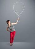 拿着气球图画的美丽的妇女 免版税库存照片