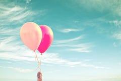 拿着气球天空背景,葡萄酒过程的孩子的手 免版税库存图片