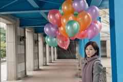 拿着气球的典雅的亚洲秀丽在桥梁下 图库摄影