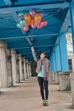 拿着气球的典雅的亚洲秀丽在桥梁下 库存照片