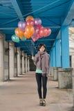 拿着气球的典雅的亚洲秀丽在桥梁下 免版税图库摄影