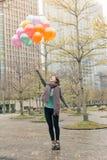拿着气球的愉快的微笑的亚裔妇女 免版税图库摄影