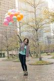 拿着气球的愉快的微笑的亚裔妇女 免版税库存照片