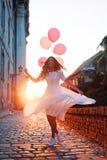 拿着气球的美丽的妇女户外 图库摄影