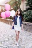 拿着气球的美丽的妇女户外 免版税库存图片