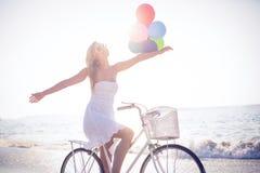 拿着气球的自行车乘驾的美丽的金发碧眼的女人 免版税库存照片