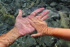 拿着水中的成人儿童现有量 免版税库存照片