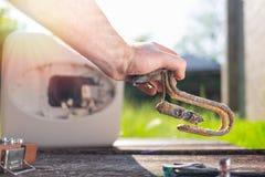 拿着水加热器元素的一个人被损坏从腐蚀 在背景中锅炉和草坪的看法 ?? ? 免版税库存照片