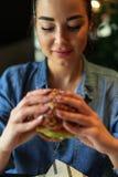 拿着水多的汉堡的年轻可爱的深色的妇女 免版税库存照片