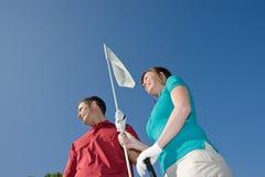 拿着水平的人针妇女的高尔夫球 免版税库存照片
