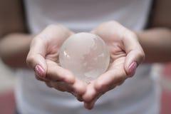 拿着水晶地球的手 库存照片