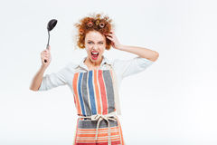 拿着汤杓子的围裙的疯狂的主妇 免版税库存图片