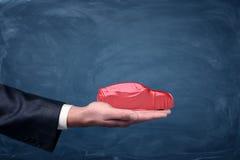 拿着汽车剪影的商人` s手用一种红色流动的织品盖 库存图片