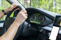 拿着汽车方向盘的男性手 在驾车的方向盘的手在湖附近 驾驶在客舱里面的人一辆汽车 免版税图库摄影