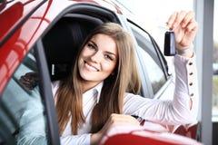 拿着汽车的妇女司机锁上在新的汽车的选址 免版税库存照片