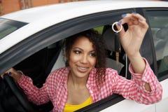 拿着汽车的幼小美丽的黑少年司机锁上驾驶她新的汽车 库存照片