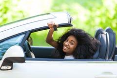 拿着汽车的幼小黑少年司机锁上驾驶她新的汽车 免版税库存照片