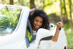 拿着汽车的幼小黑少年司机锁上驾驶她新的汽车 免版税图库摄影
