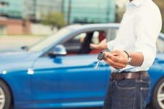 拿着汽车的男性手锁上在背景的提供的新的汽车 免版税库存照片