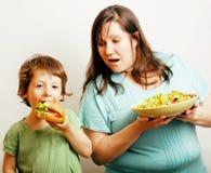 拿着沙拉和小逗人喜爱的男孩用汉堡包的成熟妇女戏弄紧密,家庭食物,生活方式真正的人民 免版税库存照片