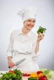 拿着沙拉的年轻微笑的厨师新鲜的荷兰芹 免版税图库摄影