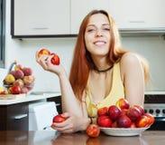 拿着油桃的愉快的妇女 免版税库存照片