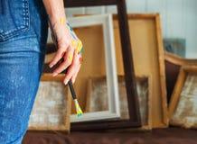 拿着油漆刷的艺术家手的特写镜头 库存图片